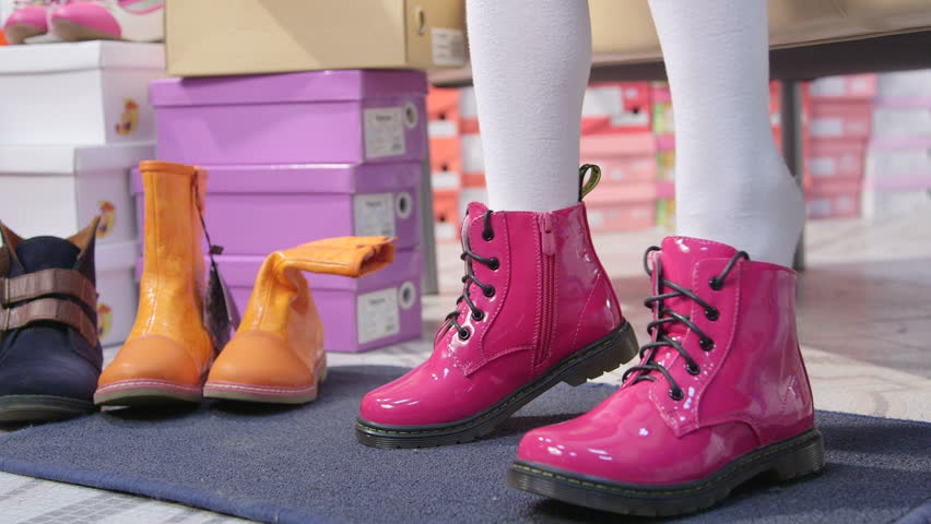 Child Trying On New Pink Combat Boots For Junior Girls In Children ...