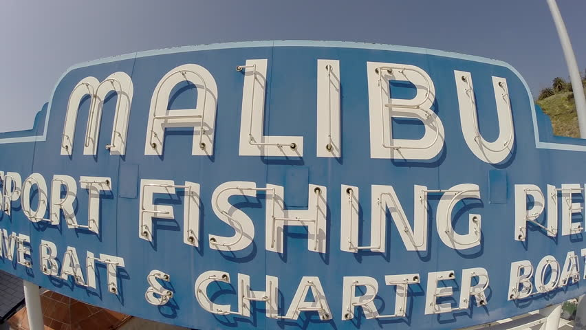 MALIBU, CALIFORNIA, USA - April 14, 2015: Clear skies above the famous Malibu sport fishing pier sign on Pacific Coast Highway in Southern California.  | Shutterstock HD Video #10035953