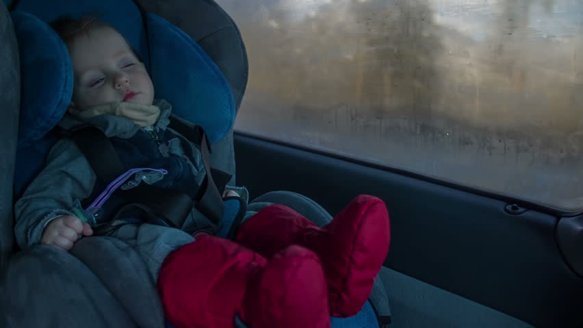 Cute boy sit in car chair. While driving on a high way the cut baby boy is slipping inn the chair on a sunny winter day footage in slow motion.