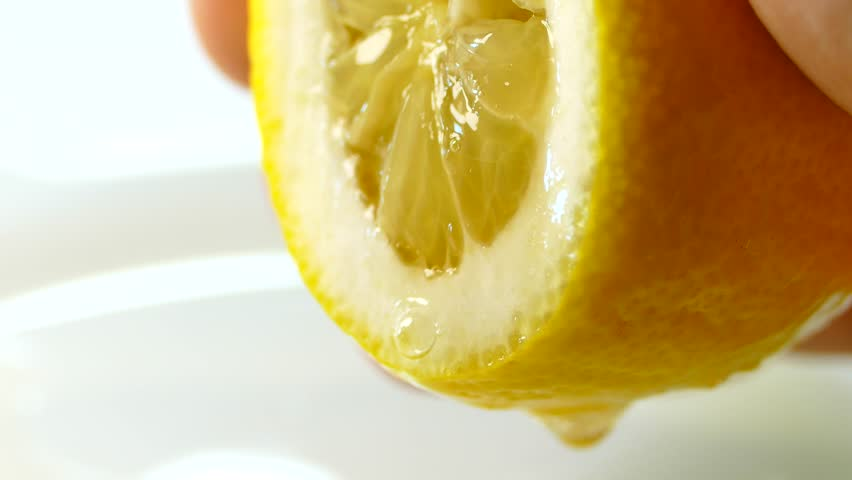Hand squeeze fresh lemon. Lemon juice drains from the pulp and drips.
