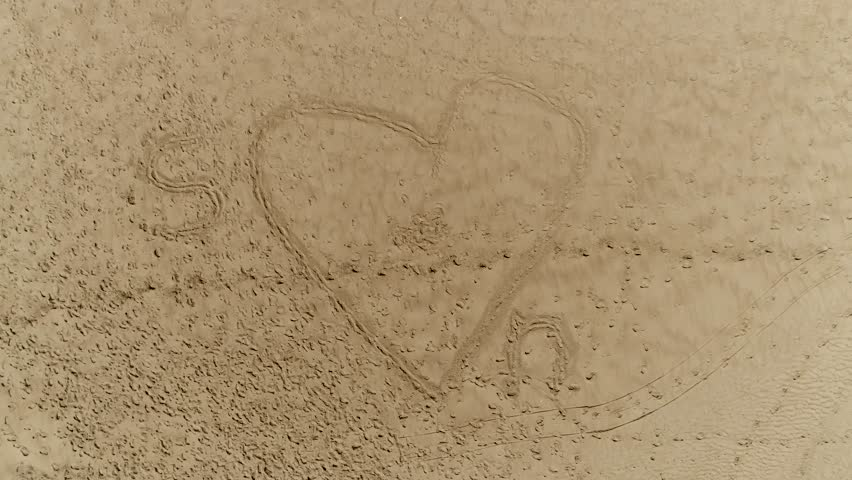 Aerial top-down view of heart beach drawing  and the letter S and N indicating S loves N background aerial footage for summer love or vacation love beautiful not too quiet beach summer scene 4k