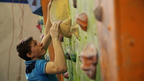 Professional boulder climbing on a steep wall and breaks down. The climbing wall. Climbing wall in the room. close-up