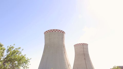 Huge cooling towers of brown coal power plant at background of industrial landscape. Nuclear power plant on the sky background in sunlight. Two cooling towers in a field in the bright sun. Industry.