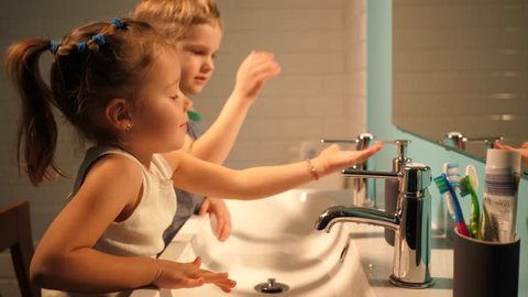 Sister and brother children in bathroom washing hands in evening family at home