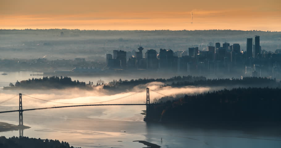 Fog moving over the ocean during sunrise under the Lionsgate Bridge. Vancouver city skyline in the backrgound, this is the viewpoint from Cypress Mountain.