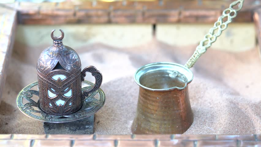 Preparation of Turkish coffee in copper Cezve on hot sand - old Turkish way of brewing coffee beverage. Turkish national drink, love him all over the world, good mood all day