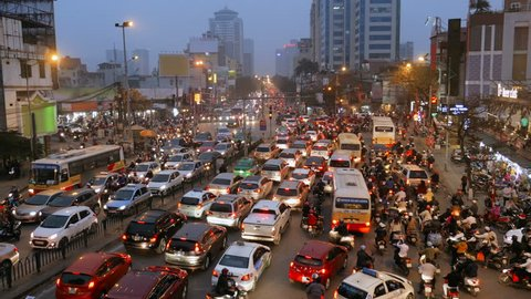 A crowded mess of motorbikes, cars and buses during rush hour at an intersection in Hanoi, Vietnam, Southeast Asia