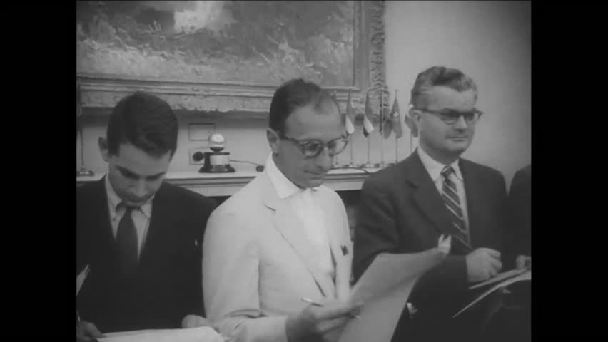 CIRCA 1957 - Journalists prepare as President Eisenhower enters a room for a speech.