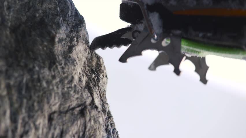 Close up of the sharp front points of a mountaineering crampon perched on a tiny rock edge, then lifting away as the climber moved up.