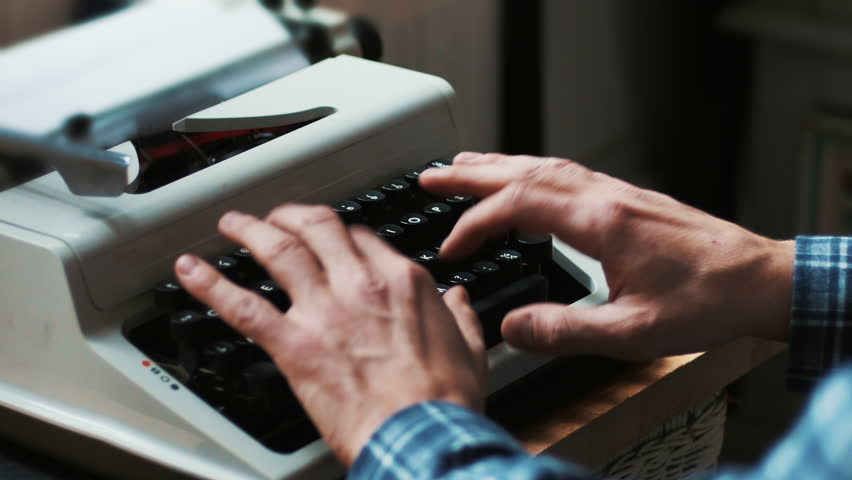 Hands typing a film script or a book on a vintage typewriter, 4k video