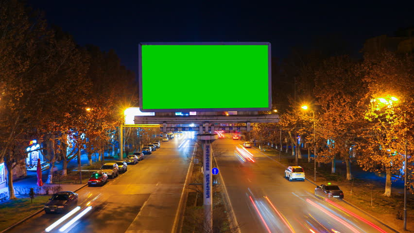 A billboard with green chroma key on a background of a city night landscape of fast moving cars with long exposure. 4K Time Lapse video