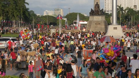 Manila,Philippines - December 25,2017: Crowds of people crossing street at Rizal monument