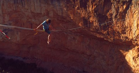 Brave young Man Slacklining , highlining above a big canyon in Chulilla , Spain . Nature Adventure and leisure sport . Mountain Balance Extreme Hiker Walking Happy, 4k aerial cinematic footage