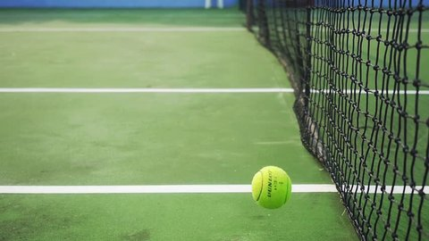 Tennis ball falling on a tennis court near the mesh. slow motion. 1920x1080. hd