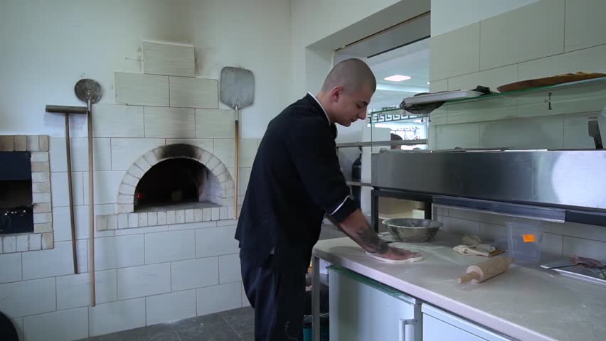 A young pizza maker prepares pizza in the kitchen of the restaurant. The cook rotates the dough in the air and spreads it on the table.