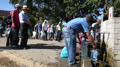 Cape Town / South Africa - January 25,  2018 : People waiting in long line to get drinking water with water bottles at Newlands natural spring in the drought in Cape Town South Africa