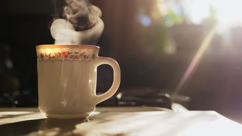 A cup of tea on the kitchen table. Morning tea. Steam evaporates in slow motion. Sunlight and glare through the kitchen window