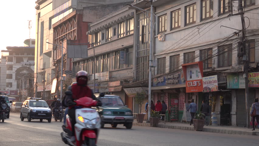 KATHMANDU, NEPAL - JAN 21: Motorbike, car and bus traffic in the inner city at sunset on January 21, 2018 in Kathmandu, Nepal