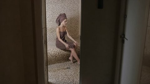Attractive woman relaxing in a hammam - turkish steam bath with ceramic tile in roman style