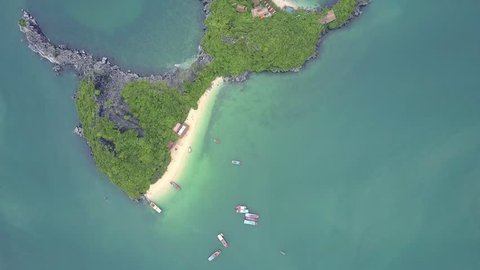 high aerial view rocky island of whimsical shape covered with tropical forest in tranquil azure bay with sailing boats