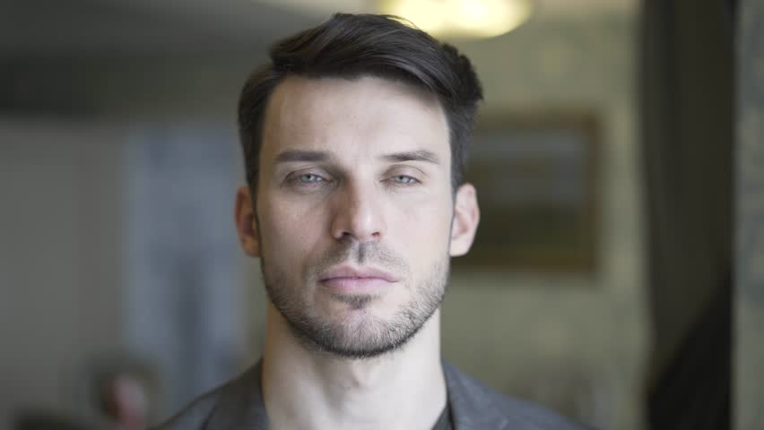 Headshot of a handsome young man with a beard turning his head to look at the viewer. Handheld real time establishing shot