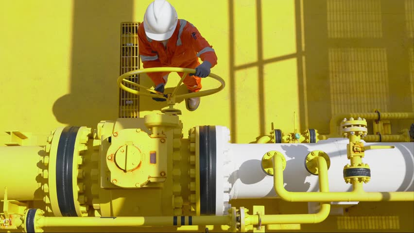 Offshore oil and gas operations, production operator open valve to allow gas flowing to sea line pipe for sent gases and crude oil to central processing platform, Remote platform site service worker.