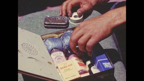 1950s: Items placed in first-aid kit. People carry items to car and pack up car.