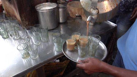 MUMBAI, INDIA - NOV 24: Indian masala chai tea being poured into glasses at stall on November 24, 2017 in Mumbai, India