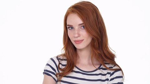 Beautiful young redhead lady looking camera isolated over white wall background showing silence gesture