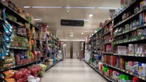 Supermarket Aisle Slow Motion. Slow motion of a shopping cart in the supermarket aisle with products and people