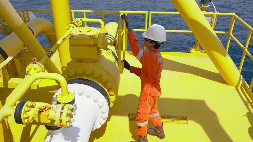 Production operator wearing personal protective equipment and opening ball valve at offshore oil and gas wellhead remote platform to control gases and crude oil process Petroleum industry occupational