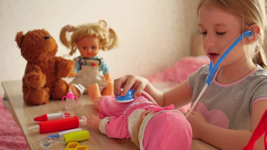 Beautiful little girl playing doctors with doll at home. | Shutterstock HD Video #1006922173