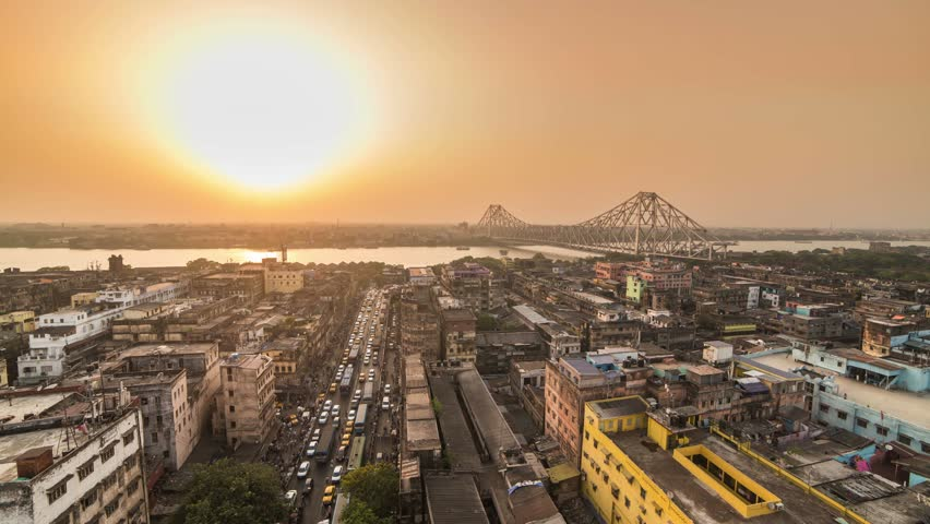 4K Timelapse of a beautiful sunset over Kolkata city with a Howrah bridge on the Ganga river, West Bengal, India.
