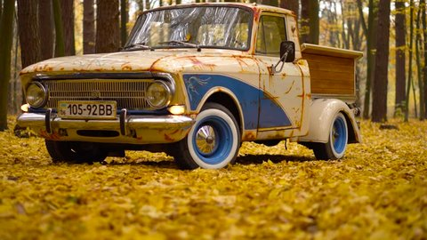Retro cars truck creative solution with blue color artificial rust and wooden luggage in a fall forest