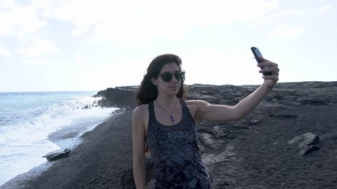 An attractive, young Armenian woman uses her smart phone to take a selfie in front of a rugged, black sand beach and rocky ocean cliffs. The blue Pacific and foamy white water meet the black shore.