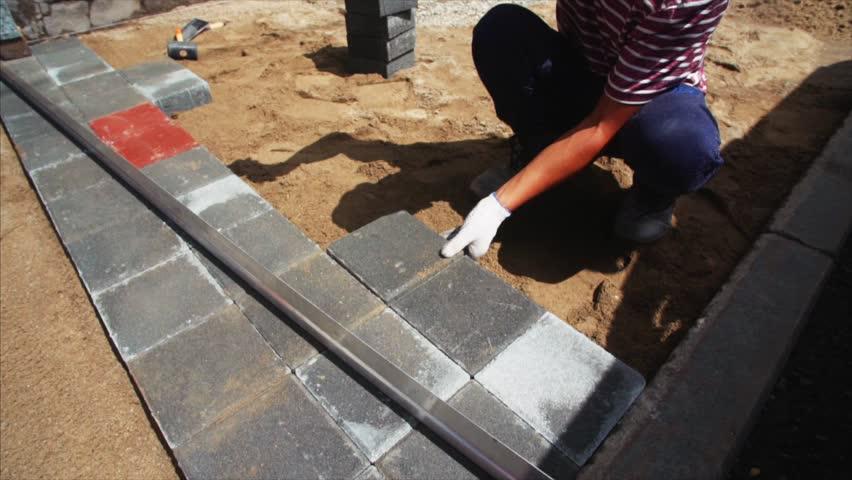 Unidentified male worker in white gloves is putting stone bricks making new sidewalk pavement