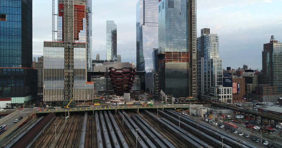 Aerial drone footage of Midtown West, New York City. The shot includes the beginning of the High Line elevated park, Hudson Yards subway storage area and newly constructed high rises. Nov 2017