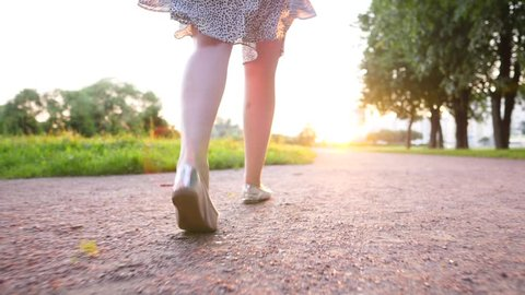 Female legs walk at gravel path, cinematic follow camera slide low behind. Fine evening sun shine ahead, vivid green colours of grass. Slender girl in summer dress have pleasure by stroll at city park