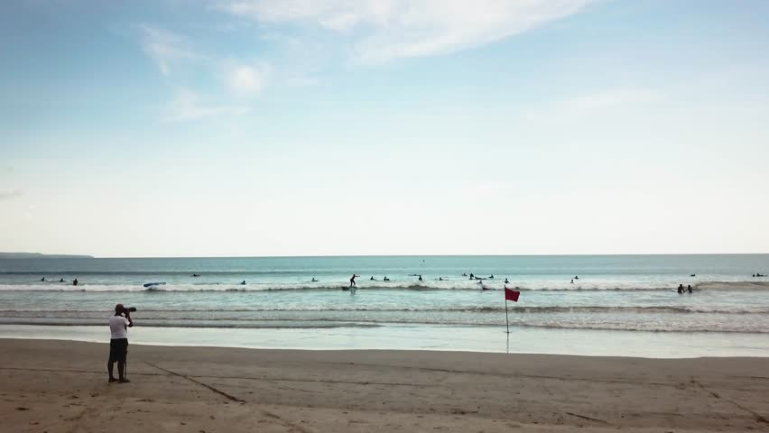 People surf on the waves. Beautiful beach on a hot day filled with people riding boards on the waves. The concept of freedom   Shutterstock HD Video #1006982143