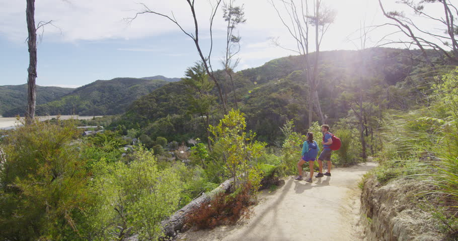 New Zealand nature landscape with hiking people tramping on travel vacation backpacking on hike. Hikers on Abel Tasman Coast Track, one of the Great Walks and tramping tracks of New Zealand. #1006989703