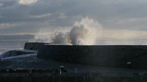 Huge wave crashes over harbour wall in slow motion, The Cobb, Lyme Regis, Dorset