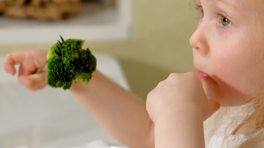 A small beautiful girl eats broccoli and green peas with pleasure, at the table at home 4k