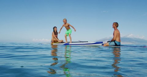 Family stand up paddle boarding having fun in the ocean