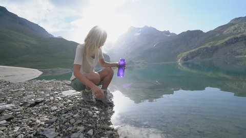 Hiking blond girl filling bottle from mountain lake. Young woman hiking gets to stunning mountain lake and refills her bottle with fresh water