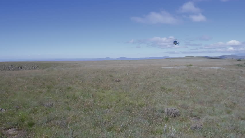 A helicopter lands on a vast mountain range