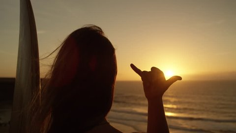 SLOW MOTION CLOSE UP: Unrecognizable girl with long flowing hair gazing at golden sunset giving the shaka sign. Female surfer making hang loose signal with her hand. Woman using Hawaiian hand gesture