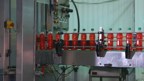 Fast moving PET bottles inside factory production line. Automatic conveyor line for filling water and juice in a plastic bottle.