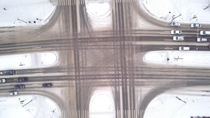 Top down perspective of street intersection at winter time, small traffic on roads. White snow lie around on pavement and sides, dark traces from vehicles on asphalt. Cars move on green light