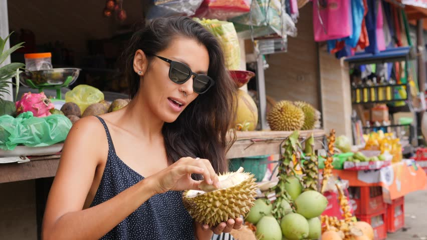 Young Mixed Race Tourist Woman Eating Exotic Durian Fruit. 4K, Bali, Indonesia.