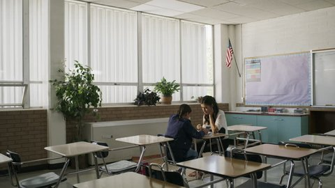 Tilt down to teacher tutoring girl after school in classroom / Provo, Utah, United States
